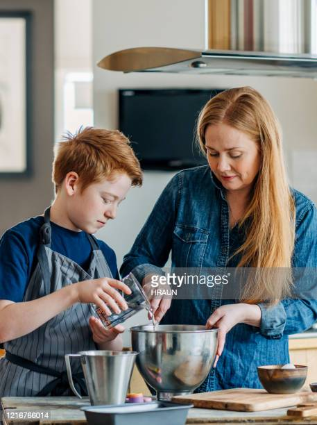 mother and son baking bread at home - zakelijke kleding stock pictures, royalty-free photos & images