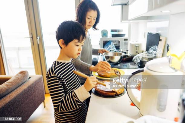 mother and son baking cake - peter lourenco stock pictures, royalty-free photos & images