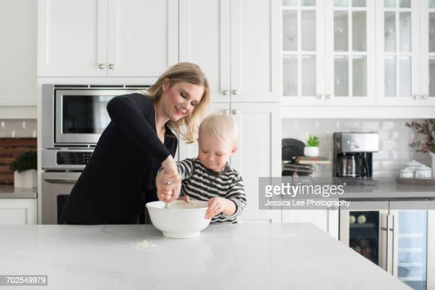Mother and son baking together, mixing mixture in mixing bowl