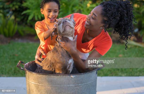 Mother and son bathing dog