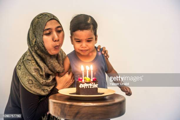 Mother and son blowing candle