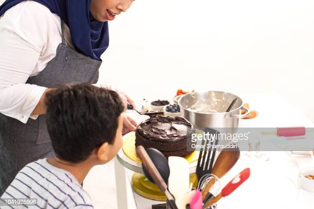 Mother and son bonding while decorating a cake