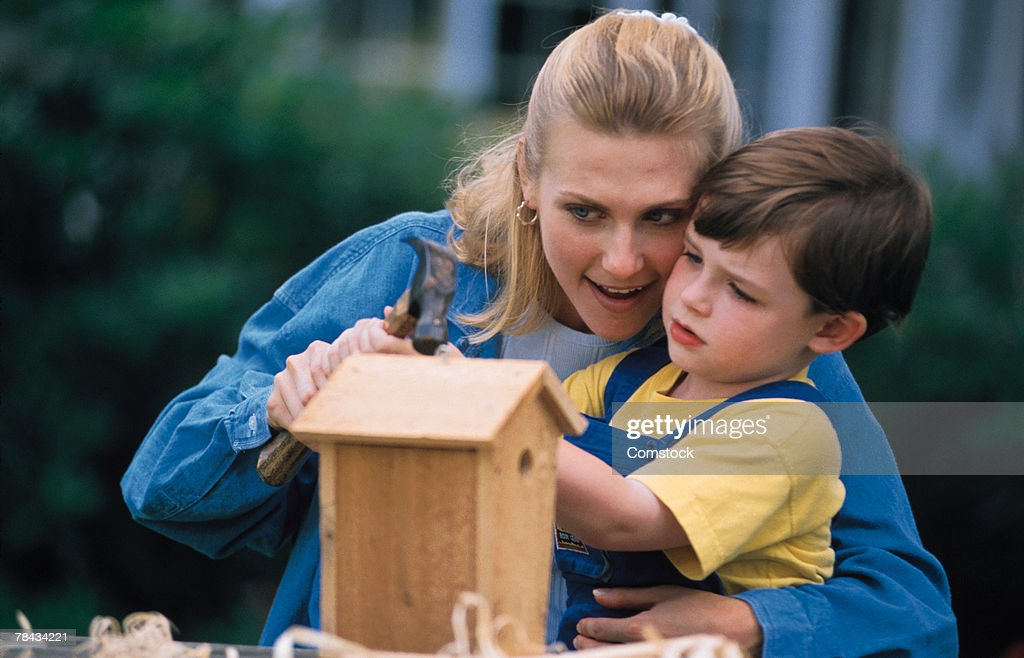 Mother and son building a birdhouse : Stockfoto