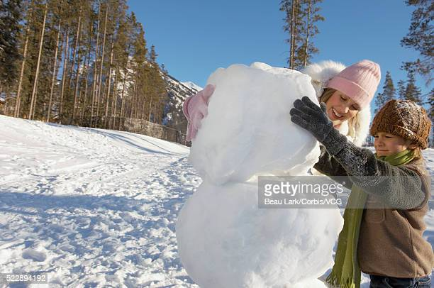 Mother and son bulding snowman