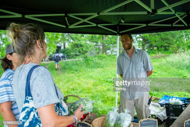 a mother and son buying fresh vegetables from a farm market - bancarella di verdura foto e immagini stock