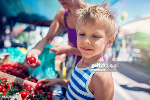 Mother and son buying tomatoes at the Italian farmer's market