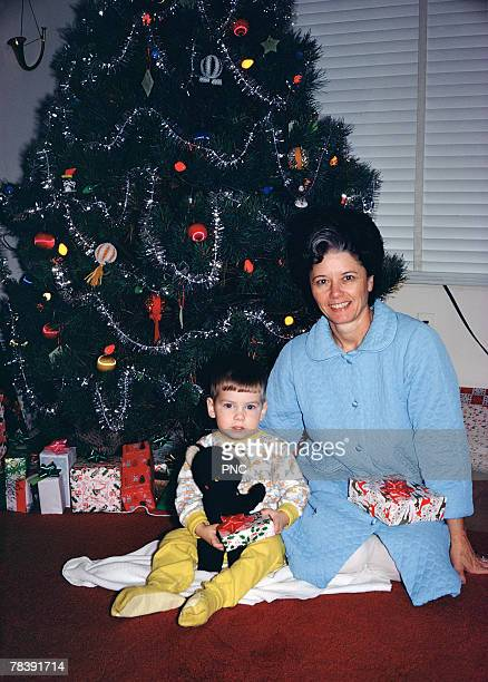 mother and son by the christmas tree - christmas past and christmas present stock pictures, royalty-free photos & images