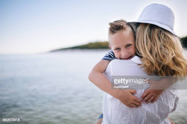mother and son by the sea - mothers day beach stock pictures, royalty-free photos & images