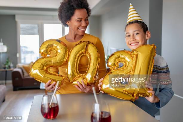 mother and son celebrating ney year 2021 at home - 2021 stock pictures, royalty-free photos & images
