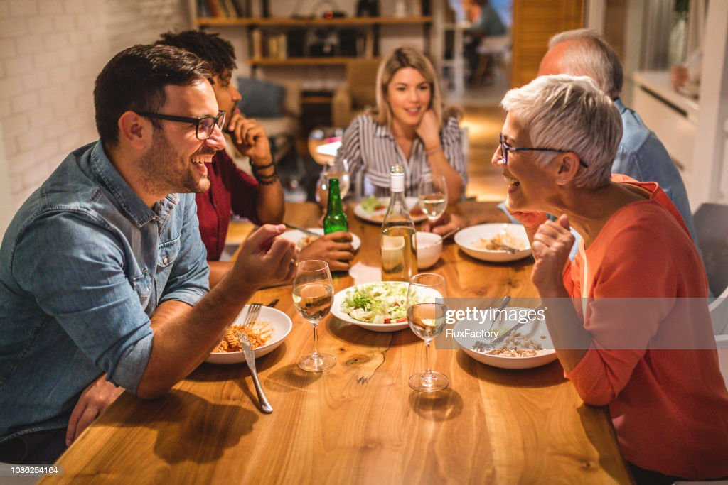 Mother and son chatting during dinner party : Stock Photo