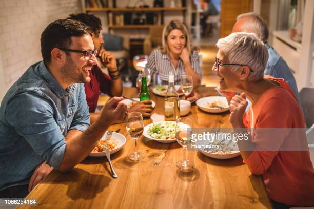mother and son chatting during dinner party - togetherness stock pictures, royalty-free photos & images