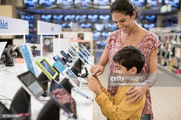 mother and son checking digital tablet in store - electronics store stock photos and pictures