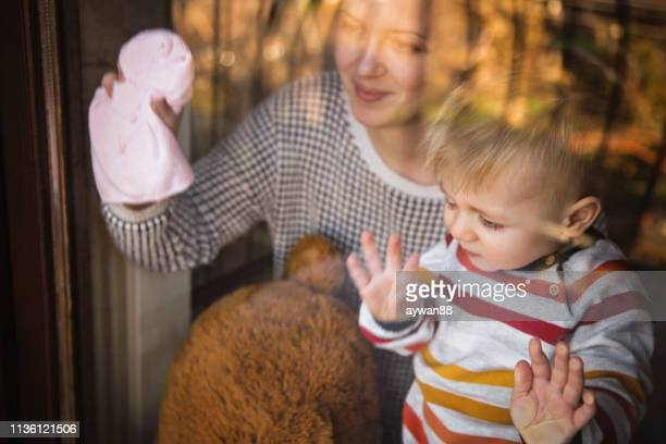 mother and son cleaning windows together - chores stock photos and pictures