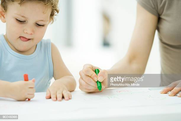 mother and son coloring with crayons together, boy sticking tongue out, cropped view - close to stock pictures, royalty-free photos & images