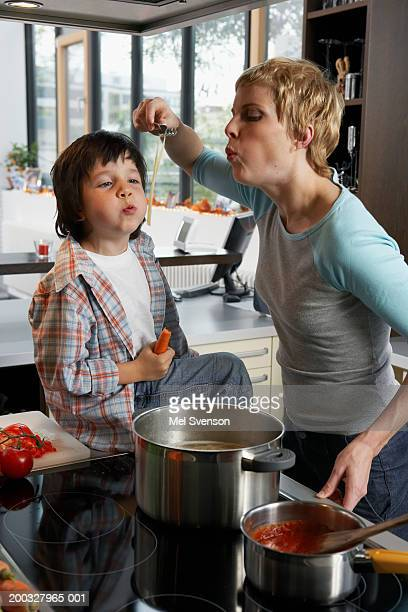 Mother and son (5-7) cooking, blowing on spaghetti
