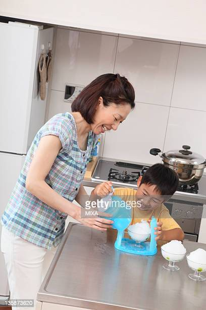 Mother and son cooking shaved ice together