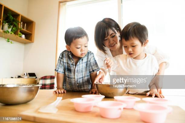 mother and son cooking together - aziatische etniciteit stockfoto's en -beelden