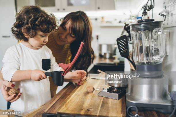 mother and son cracking a walnut - household equipment stock pictures, royalty-free photos & images