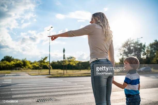 mother and son crossing the road - crossing stock pictures, royalty-free photos & images