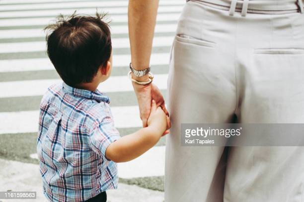 mother and son crossing the street - fesse enfant photos et images de collection