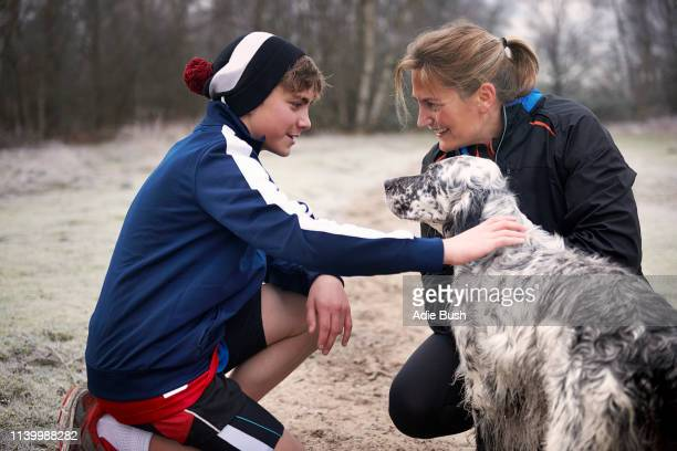 mother and son crouching down stroking dog, face to face smiling - bush dog stock pictures, royalty-free photos & images