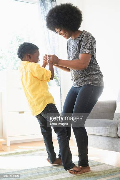 mother and son (6-7) dancing in living room - black male feet stock photos and pictures