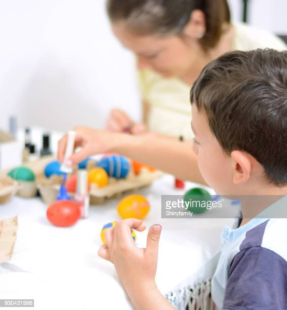 Mother and son decorating Easter eggs