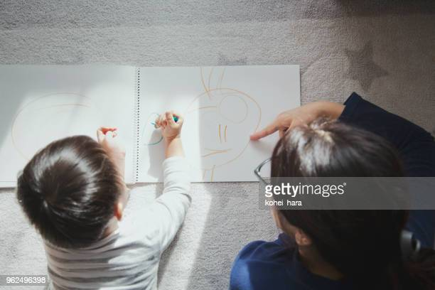 Madre e hijo dibujando un cuadro en casa