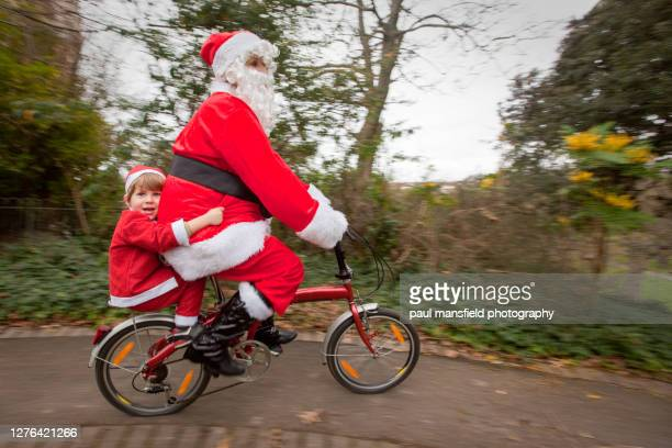 mother and son dressed as santa claus on a bicycle - father christmas stock pictures, royalty-free photos & images