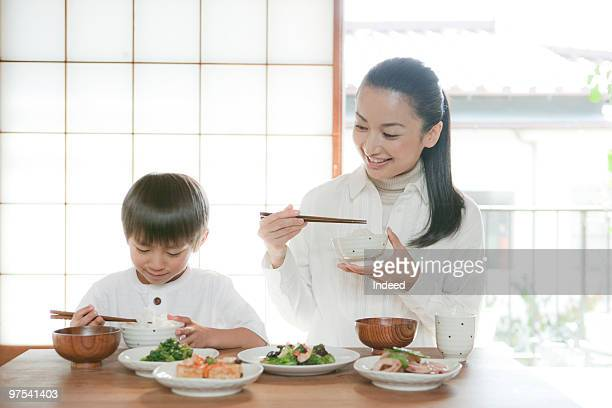 Mother and son(4-5) eating Japanese food