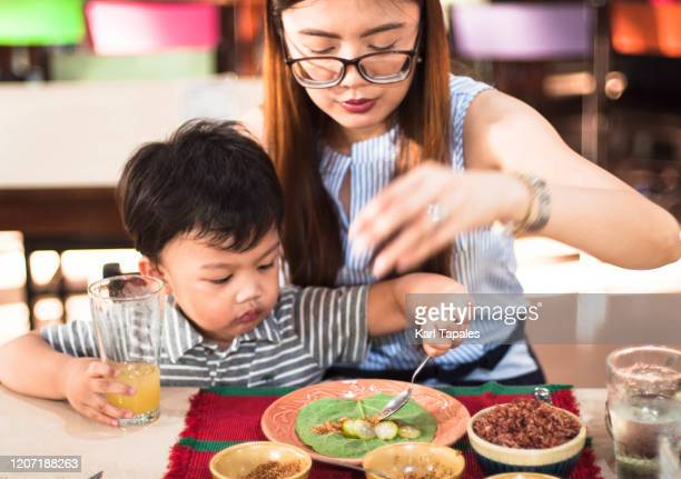 mother and son eating local leafy green salad - filipino family eating stock pictures, royalty-free photos & images