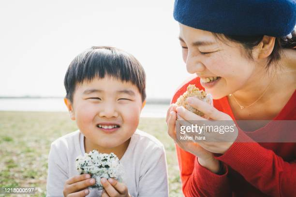 Mother and son eating rice bowl in the park