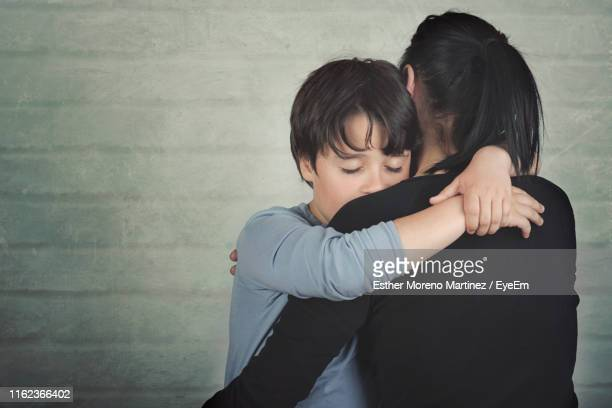 mother and son embracing against wall - sad child stock pictures, royalty-free photos & images