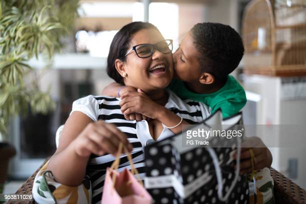 mother and son embracing and receiving gifts - mothers or children's day - affectionate stock pictures, royalty-free photos & images