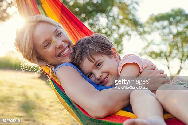 Mother and son embracing in hammock, portrait