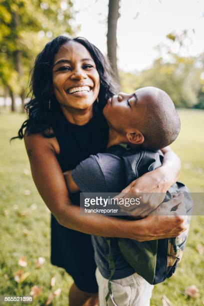 mother and son embracing in the park - mother and son stock photos and pictures