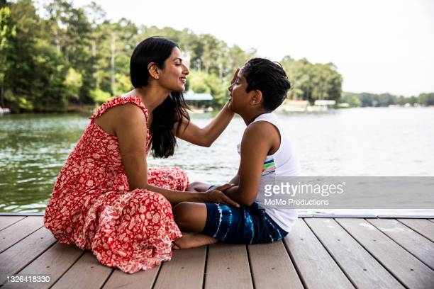 mother and son embracing on dock at lake - sleeveless dress stock pictures, royalty-free photos & images