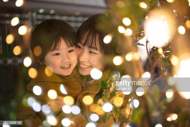 mother and son enjoying christmas lights - illuminated stock pictures, royalty-free photos & images