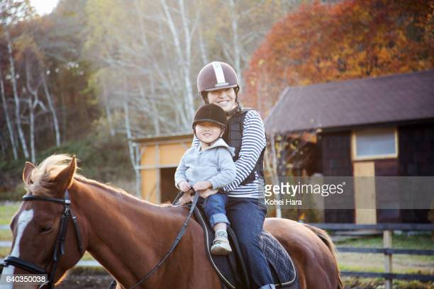 Mother and son enjoying horse-riding together in pasture