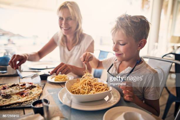 Mother and son enjoying meal in hotel restaurant