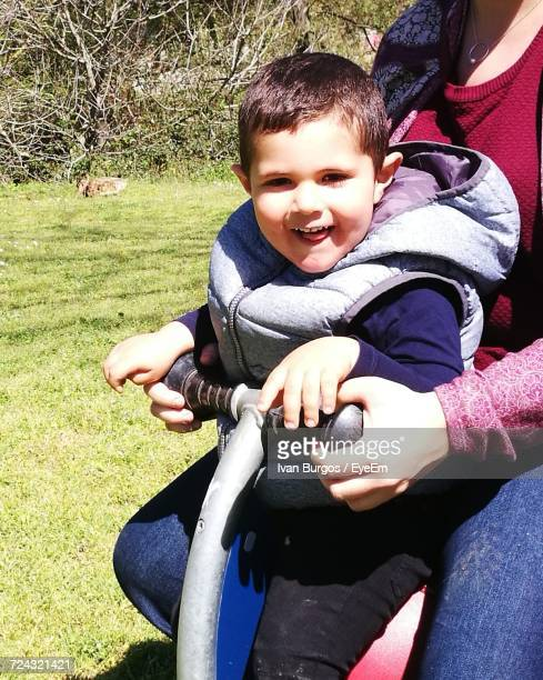 Mother And Son Enjoying Spring Ride At Park