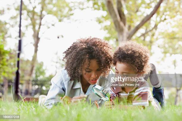 Mother and son examining grass in park