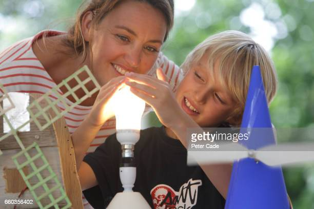mother and son experimenting with windmill power - western europe stock pictures, royalty-free photos & images