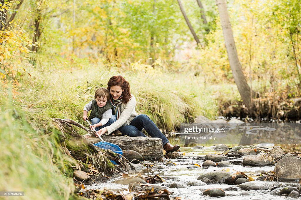 Mother and son (4-5) fishing in mountain stream : Bildbanksbilder