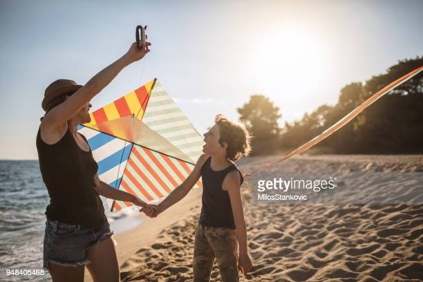 mother and son flying a kite at the beach - kite toy stock pictures, royalty-free photos & images