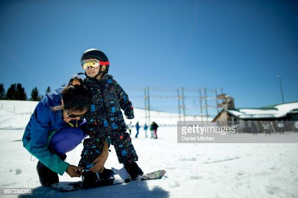 Mother and son getting ready to snowboard.