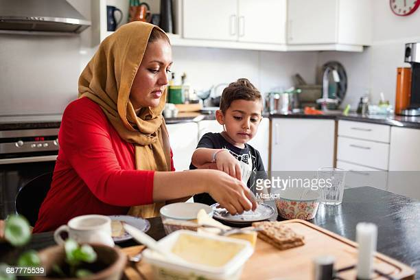 mother and son having breakfast at dining table in kitchen - cracker snack stock photos and pictures