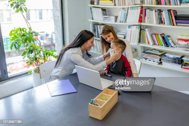 mother and son having consultation with female paediatrician in hospital office - family politics stock pictures, royalty-free photos & images