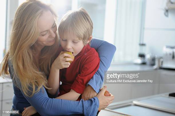 Mother and son having fruit in kitchen