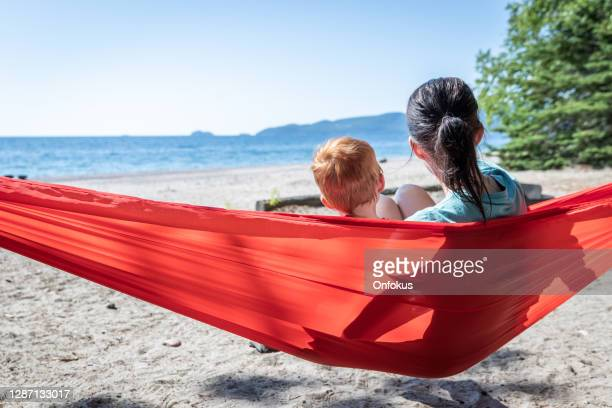mother and son having fun in red hammock at campground in summer, ontario, canada - lake superior provincial park stock pictures, royalty-free photos & images